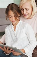Woman assisting her daughter in using a digital tablet Stock Photo - Premium Royalty-Freenull, Code: 6108-05870095