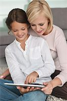 Woman assisting her daughter in using a digital tablet Stock Photo - Premium Royalty-Freenull, Code: 6108-05870103