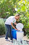 Woman throwing papers in garbage bin Stock Photo - Premium Royalty-Freenull, Code: 6108-05870271
