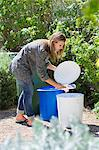 Woman throwing papers in garbage bin Stock Photo - Premium Royalty-Freenull, Code: 6108-05870293