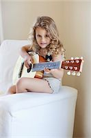 Portrait of a cute little girl playing a guitar Stock Photo - Premium Royalty-Freenull, Code: 6108-05870434
