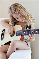 Cute little girl playing a guitar Stock Photo - Premium Royalty-Freenull, Code: 6108-05870481