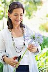 Smiling woman pruning a flower