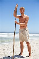 shirtless men - Man standing on the beach with a stick Stock Photo - Premium Royalty-Freenull, Code: 6108-05871039