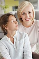 Portrait of a woman sitting with her daughter and smiling Stock Photo - Premium Royalty-Freenull, Code: 6108-05871199