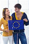 Couple holding European union flag at an airport and looking at each other Stock Photo - Premium Royalty-Free, Artist: RelaXimages, Code: 6108-05871274