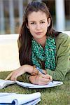 Portrait of young woman lying on grass and studying in a campus Stock Photo - Premium Royalty-Freenull, Code: 6108-05871312