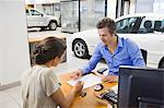 Mid adult man buying car in a showroom Stock Photo - Premium Royalty-Free, Artist: Robert Harding Images, Code: 6108-05871379
