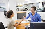 Saleswoman handling car key to a man Stock Photo - Premium Royalty-Freenull, Code: 6108-05871399