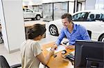 Mid adult man buying car in a showroom Stock Photo - Premium Royalty-Free, Artist: Robert Harding Images, Code: 6108-05871417
