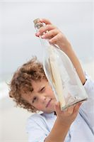 Boy looking at message in a bottle on beach Stock Photo - Premium Royalty-Freenull, Code: 6108-05871585