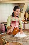 Smiling senior woman pouring water in flour Stock Photo - Premium Royalty-Free, Artist: Photocuisine, Code: 6108-05871810