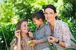 Happy mother eating fruits with her two daughters outdoors Stock Photo - Premium Royalty-Freenull, Code: 6108-05871942