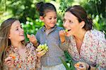 Happy mother eating fruits with her two daughters outdoors Stock Photo - Premium Royalty-Freenull, Code: 6108-05871957