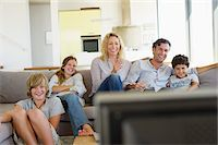 Family watching TV together at home Stock Photo - Premium Royalty-Freenull, Code: 6108-05872039