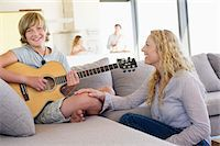 Teenage boy playing a guitar with his mother sitting near him and smiling Stock Photo - Premium Royalty-Freenull, Code: 6108-05872043