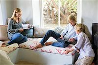 Children using digital tablet while mother reading magazine at house Stock Photo - Premium Royalty-Freenull, Code: 6108-05872052