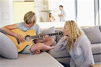 Teenage boy playing a guitar and his mother listening Stock Photo - Premium Royalty-Freenull, Code: 6108-05872054