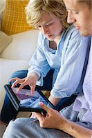 preteen touch - Man and a little boy looking at digital tablet Stock Photo - Premium Royalty-Freenull, Code: 6108-05872057
