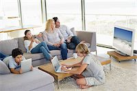 Couple watching television set while kids busy using electronic gadgets Stock Photo - Premium Royalty-Freenull, Code: 6108-05872060