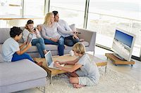 Couple watching television set while their children busy in different activities Stock Photo - Premium Royalty-Freenull, Code: 6108-05872070