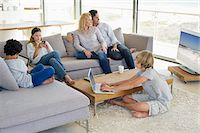 Couple watching television set while their children busy in different activities Stock Photo - Premium Royalty-Freenull, Code: 6108-05872083