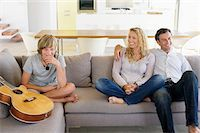 Family sitting on a couch and smiling Stock Photo - Premium Royalty-Freenull, Code: 6108-05872089