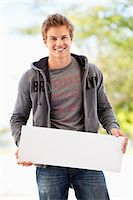 person holding sign - Portrait of a man holding a blank placard Stock Photo - Premium Royalty-Freenull, Code: 6108-05872157