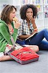 University student looking at her friend eating food in a library Stock Photo - Premium Royalty-Freenull, Code: 6108-05872293