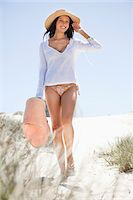 Young woman walking on the beach Stock Photo - Premium Royalty-Freenull, Code: 6108-05872471
