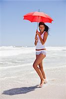 Woman walking on the beach with an umbrella Stock Photo - Premium Royalty-Freenull, Code: 6108-05872492