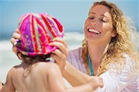 Woman putting a cap on her daughter head Stock Photo - Premium Royalty-Freenull, Code: 6108-05872554