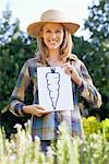 Portrait of a young woman showing carrot painting in a field Stock Photo - Premium Royalty-Free, Artist: CulturaRM, Code: 6108-05872573