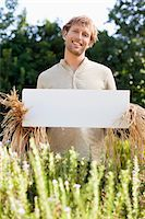 person holding sign - Young man in scarecrow dressing and holding a blank placard in a field Stock Photo - Premium Royalty-Freenull, Code: 6108-05872578