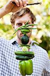 Man holding vegetables hanging on a twig Stock Photo - Premium Royalty-Free, Artist: Photocuisine, Code: 6108-05872650