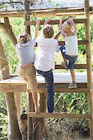 Rear view of children climbing ladders to tree house Stock Photo - Premium Royalty-Freenull, Code: 6108-05872657