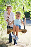 swing (sports) - Smiling little siblings playing in tree swing Stock Photo - Premium Royalty-Freenull, Code: 6108-05872666