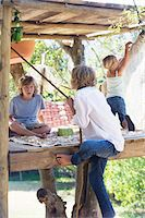 Rear view of a boy grasping rope to reach tree house Stock Photo - Premium Royalty-Freenull, Code: 6108-05872718