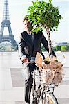 Businessman carrying a plant on a bicycle with the Eiffel Tower in the background, Paris, Ile-de-France, France Stock Photo - Premium Royalty-Free, Artist: Garry Black, Code: 6108-05872848