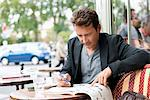 Man reading a magazine in a restaurant, Paris, Ile-de-France, France Stock Photo - Premium Royalty-Free, Artist: Andrew Kolb, Code: 6108-05872905