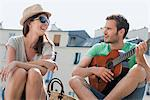 Man playing a guitar with a woman smiling, Canal St Martin, Paris, Ile-de-France, France Stock Photo - Premium Royalty-Free, Artist: ableimages, Code: 6108-05873061