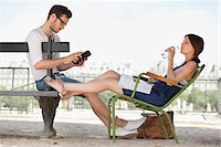 people sitting on bench - Woman drinking water and her husband using a digital tablet, Jardin des Tuileries, Paris, Ile-de-France, France Stock Photo - Premium Royalty-Freenull, Code: 6108-05873067