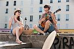 Man playing a guitar with a woman clapping and smiling, Canal St Martin, Paris, Ile-de-France, France Stock Photo - Premium Royalty-Free, Artist: Ikon Images, Code: 6108-05873089