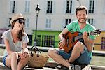 Man playing a guitar with a woman smiling, Canal St Martin, Paris, Ile-de-France, France Stock Photo - Premium Royalty-Free, Artist: ableimages, Code: 6108-05873103