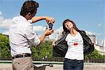 Man taking a picture of a woman with a mobile phone, Seine River, Paris, Ile-de-France, France Stock Photo - Premium Royalty-Free, Artist: ableimages, Code: 6108-05873128