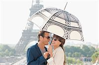 Couple under an umbrella with the Eiffel Tower in the background, Paris, Ile-de-France, France Stock Photo - Premium Royalty-Freenull, Code: 6108-05873139