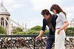 Couple locking a padlock of love on a bridge, Pont des Arts, Notre Dame de Paris, Paris, Ile-de-France, France Stock Photo - Premium Royalty-Free, Artist: Robert Harding Images, Code: 6108-05873158