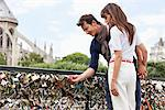 Couple locking a padlock of love on a bridge, Pont des Arts, Notre Dame de Paris, Paris, Ile-de-France, France Stock Photo - Premium Royalty-Free, Artist: ableimages, Code: 6108-05873169