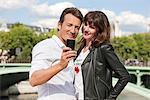 Couple taking a picture of themselves with a mobile phone, Seine River, Paris, Ile-de-France, France Stock Photo - Premium Royalty-Free, Artist: ableimages, Code: 6108-05873193