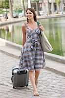 Woman pulling a suitcase and smiling, Paris, Ile-de-France, France Stock Photo - Premium Royalty-Freenull, Code: 6108-05873205